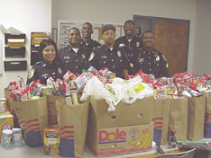 Some of the volunteers who turned out to prepare and deliver 41 Christmas food baskets. Front row, left to right: Officers Tomasa Martinez, Cedric Davis, Warren Mays and Sgt. Arthur Smith. Back row, left to right: Sgt. Albert Monk, Corporal Rufus Johnson.