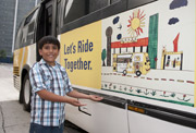 Poster contest winner Erik Garcia shows off one of the buses carrying his art across the DART Service Area.
