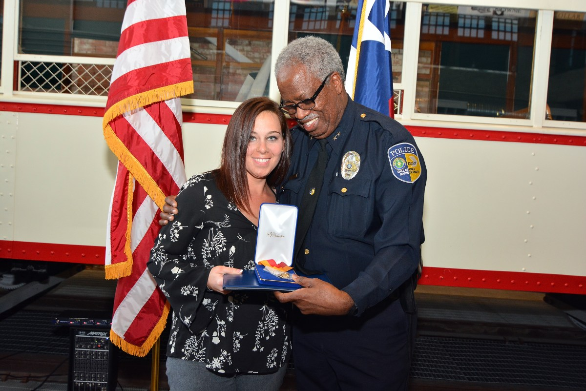 Officer Brent Thompson's wife, Officer Emily Thompson, accepts DART's Medal of Honor from Police Chief James Spiller