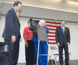 Mrs. Jack Hatchell unveils the new transit center plaque while DART President and Executive Director Gary Thomas, DART Board Chairman Randall Chrisman, DART Board member Faye Wilkins and City of Plano Mayor Phil Dyer look on.