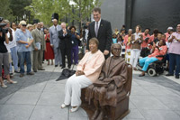 US Rep. Eddie Bernice Johnson takes a seat next to civil rights pioneer Rosa Parks. The statue is the centerpiece of a new bus passenger facility in Downtown Dallas.