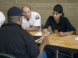 Image of a Hurricane Katrina evacuee with DART personnel at Reunion Arena