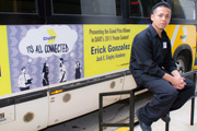 Poster contest winner Erick Gonzalez with one of the buses displaying his art across the DART Service Area.
